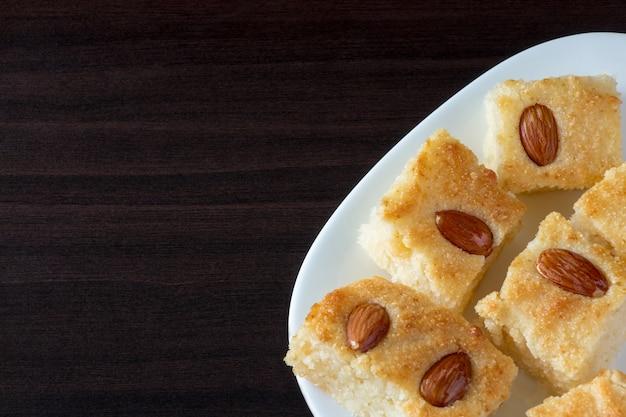 Basbousa (namoora) pastel de sémola árabe tradicional con almendras y jarabe. fondo oscuro