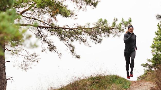 Basculador deportivo femenino corriendo en la naturaleza