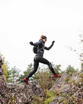 Basculador deportivo femenino saltando piedras