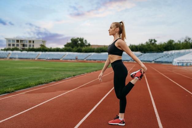 Basculador femenino en ropa deportiva, entrenamiento en el estadio. mujer haciendo ejercicio de estiramiento antes de correr en la arena al aire libre