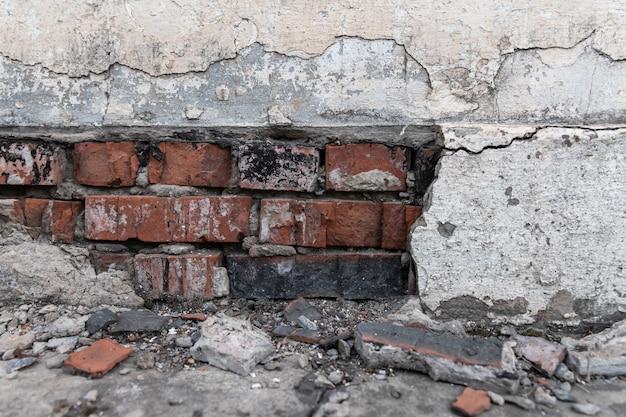 La base de un edificio residencial se derrumba gradualmente. grietas en los cimientos. el yeso se cae de una pared de ladrillos debido al impacto de los factores climáticos.