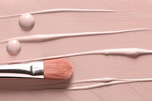 Base líquida manchada y pincel de maquillaje
