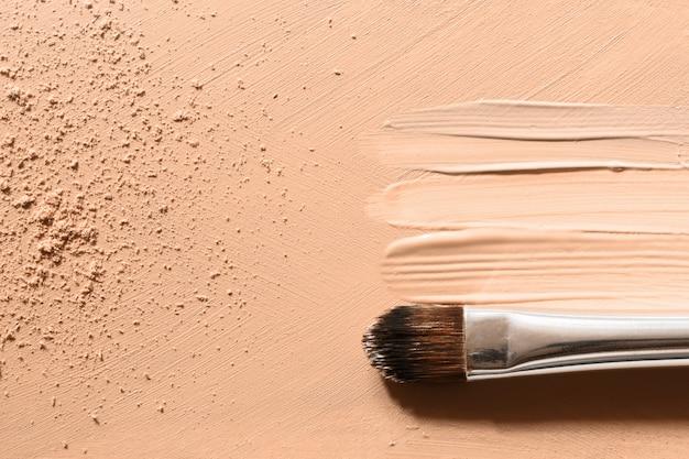 Base de maquillaje, manchas de corrector beige, polvos faciales y pincel de maquillaje cosmético