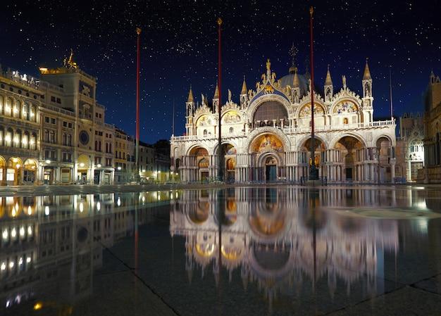 Basílica en la plaza san marco en venecia con reflexión sobre la noche de marea alta