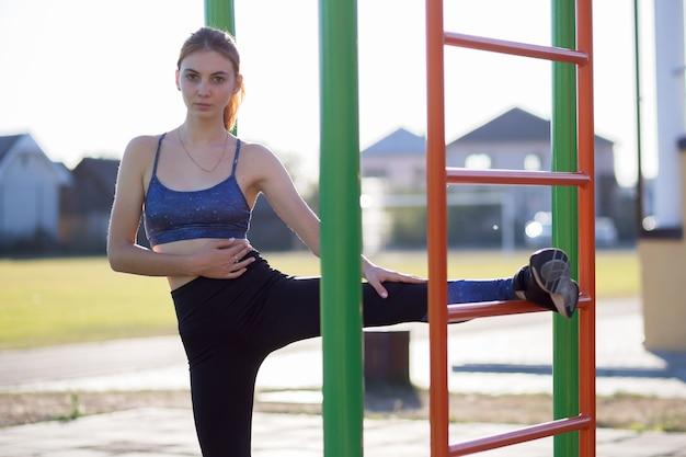 Bastante adolescente haciendo ejercicios de fitness en el estadio al aire libre. la mujer joven está estirando sus piernas antes de correr.