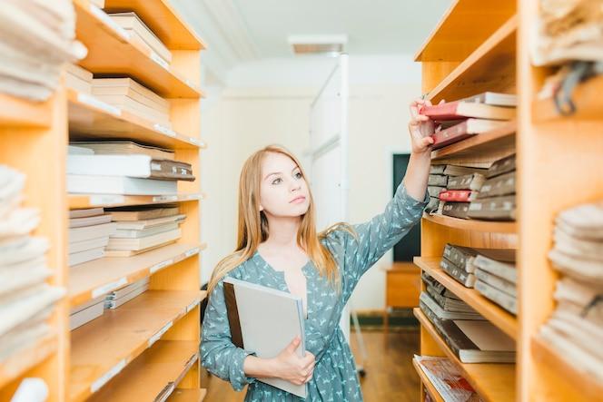 Bastante adolescente tomando libros de texto del estante
