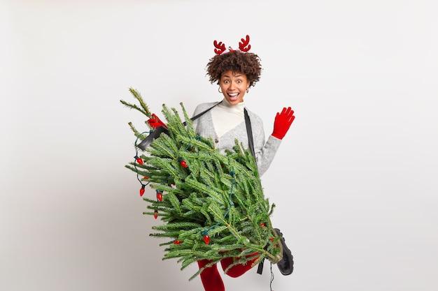 Bastante alegre adolescente afroamericana levanta la mano y la pierna baila despreocupadamente sostiene el abeto como si el instrumento musical pretendiera ser un guitarrista profesional viste un disfraz de navidad se divierte en la fiesta