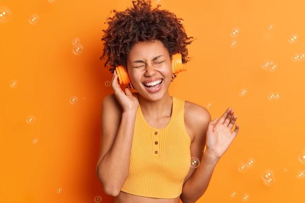 Bastante alegre adolescente de piel oscura escucha música a través de auriculares cierra los ojos y sonríe ampliamente