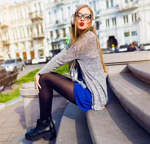 Bastante alegre joven con elegantes auriculares disfrutando de su música favorita, sonriendo, posando en pasos, calles del centro de la ciudad. cabello largo y rubio.