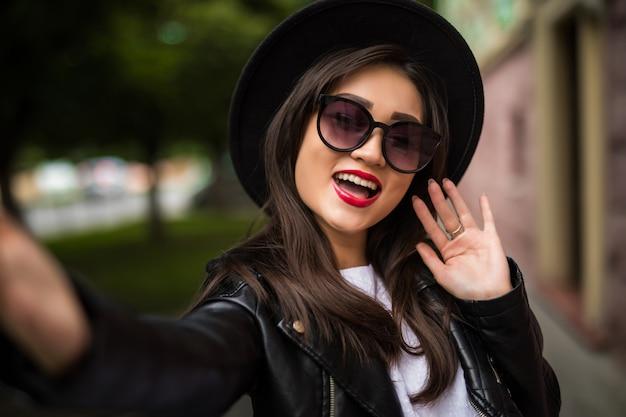 Bastante hermosa mujer asiática sonriente con sombrero y gafas de sol tomando selfie en calle de la ciudad