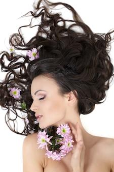 Bastante hermosa niña acostada con flores brillantes en su cabello maquillaje brillante aislado en blanco