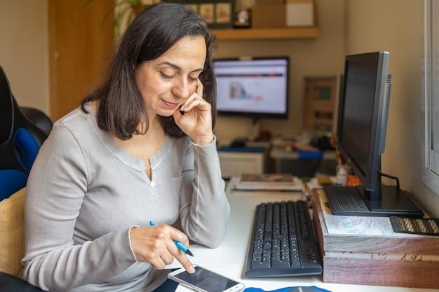 Bastante hispana mujer de mediana edad estudiando curso en línea en casa