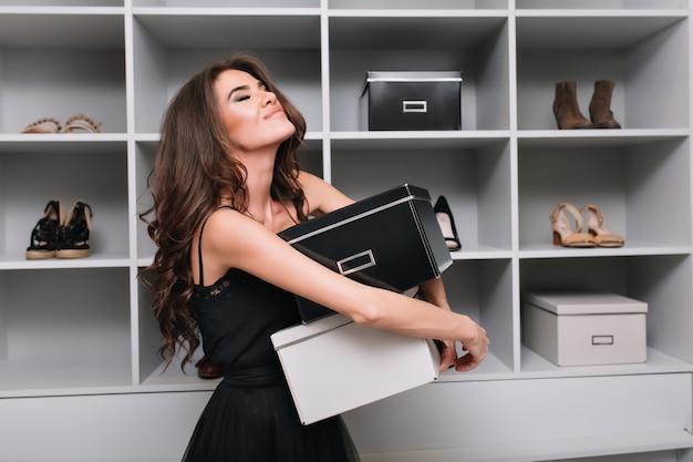 Bastante joven abrazando cajas de zapatos alrededor de elegante vestidor, armario. está muy feliz, contenta, ha cerrado los ojos, compró lo que quería. lleva un vestido negro, tiene el pelo largo y rizado.