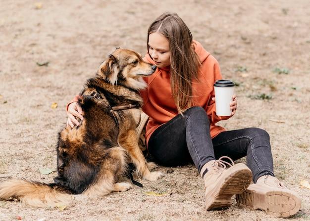 Bastante joven acariciando a su perro