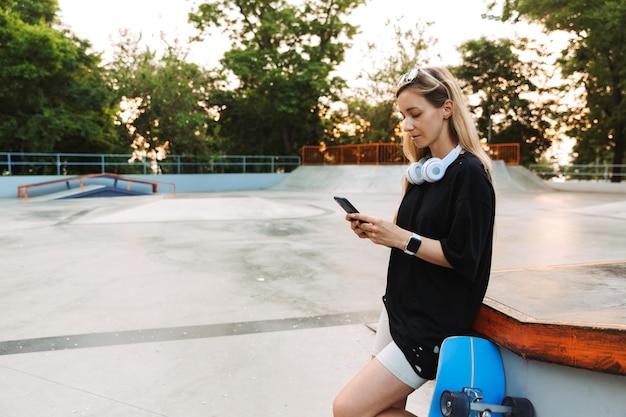 Bastante joven adolescente de pie en el skatepark con un longboard, sosteniendo un teléfono móvil