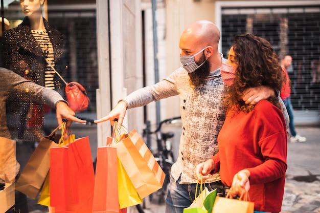 Bastante joven apuntando al escaparate para mostrar el artículo de ropa que le gusta a su novia - hermosa joven pareja disfrutando de compras, divirtiéndose juntos, con la mascarilla