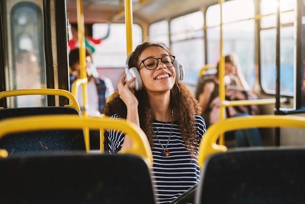 Bastante joven con auriculares sentado en un autobús y mirando la tableta.