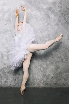 Bastante joven bailarina bailando ballet clásico contra la pared rústica