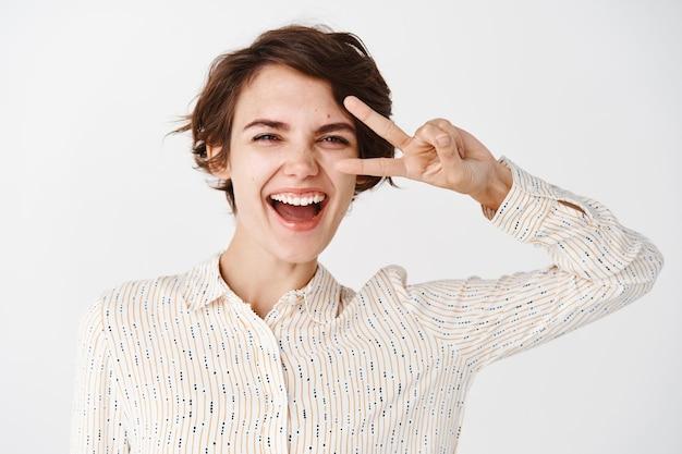 Bastante joven en blusa mostrando el signo de la paz sobre los ojos y riendo, feliz de pie contra la pared blanca