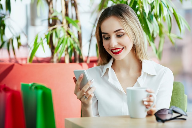 Bastante joven con cabello castaño claro y labios rojos con blusa blanca y sentada con coloridas bolsas de compras y taza de café, sosteniendo el teléfono móvil, concepto de compras.