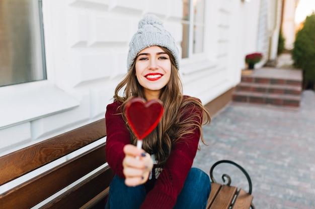 Bastante joven con cabello largo sentado en un banco en la calle. ella estira el corazón de caramelo y sonríe.