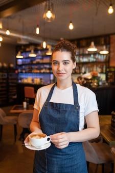 Bastante joven camarera morena con taza de capuchino de pie delante de la cámara sobre fondo de mesas y sillas en el café