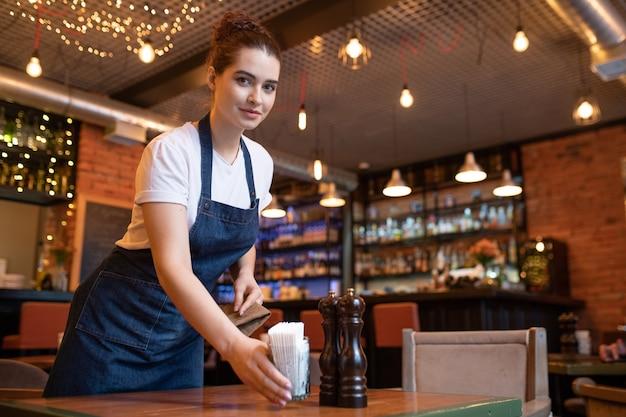 Bastante joven camarera en ropa de trabajo inclinada sobre la mesa mientras pone vidrio con palillos de dientes y le mira en la cafetería o restaurante