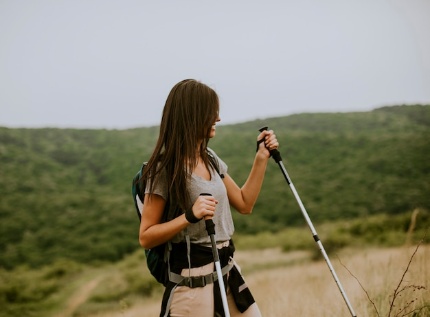 Bastante joven caminando con mochila sobre colinas verdes en un día de verano