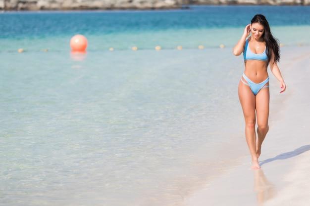 Bastante joven caminando en una playa de arena en bikini y disfrutando del sol