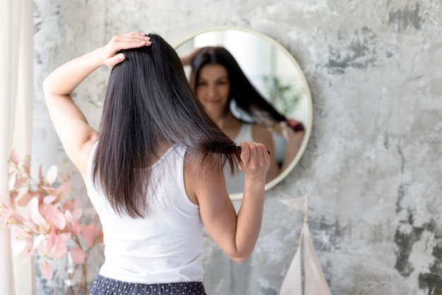 Bastante joven cepillando su cabello