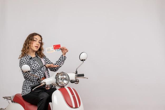 Bastante joven en ciclomotor con billete y tarjeta en gris