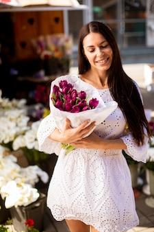 Bastante joven comprando flores en el mercado de las flores
