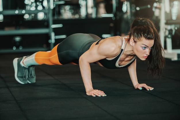 Bastante joven culturista mujer caucásica con cola de caballo haciendo flexiones en el piso del gimnasio.
