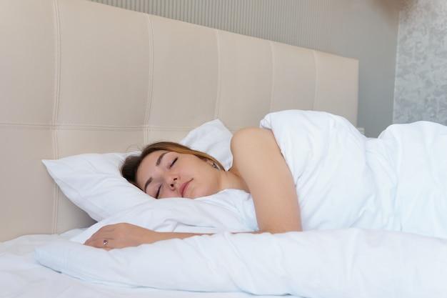 Bastante joven se despierta en una cama grande en el hotel.