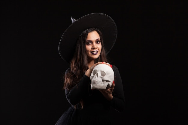 Bastante joven en un disfraz de bruja para la fiesta de halloween haciendo brujería malvada. retrato de mujer haciendo magia en un cráneo humano.