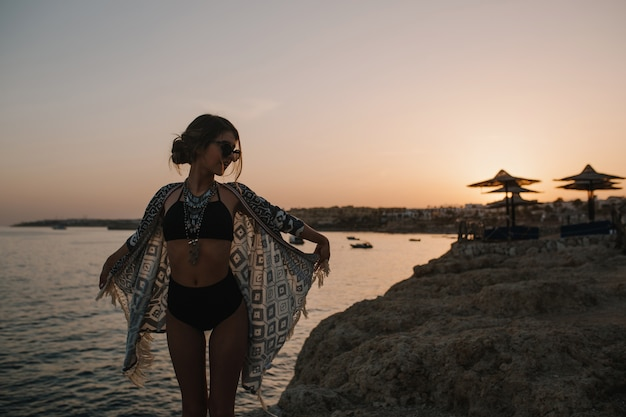Bastante joven disfrutando del atardecer en la playa con rocas, tener vacaciones. mirando a un lado. el uso de elegantes gafas de sol, traje de baño negro de moda, bikini, chaqueta de punto, capa con adornos.