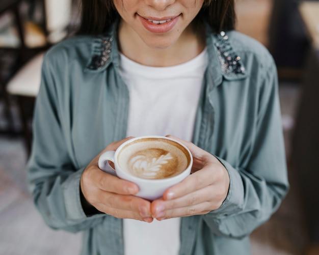 Bastante joven disfrutando de una taza de café