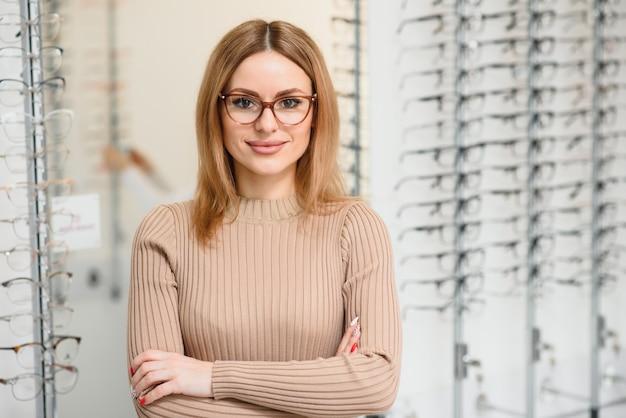 Bastante joven está eligiendo gafas nuevas en la tienda de óptica
