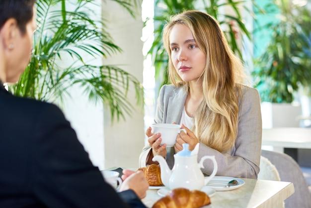 Bastante joven empresaria bebiendo café durante la reunión en el café