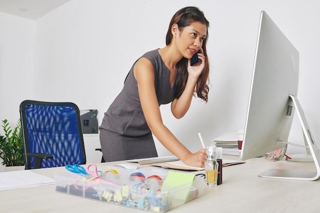 Bastante joven empresaria de pie en su escritorio, hablando por teléfono con el cliente y tomando notas en el planificador