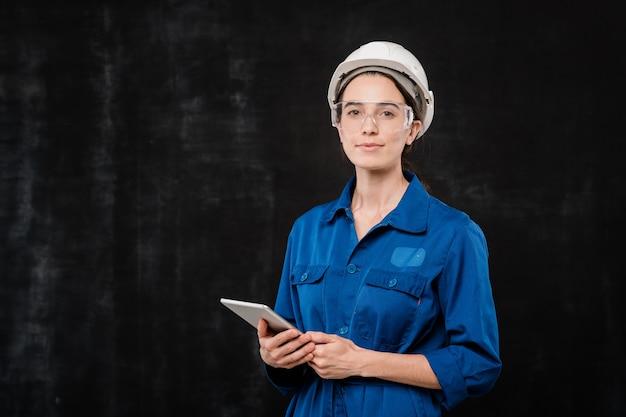 Bastante joven especialista en casco y ropa de trabajo azul usando el panel táctil mientras está parado frente a la cámara de forma aislada