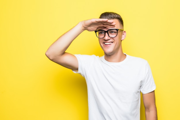 Bastante joven espera vestido con camiseta blanca y gafas transparentes aisladas en amarillo