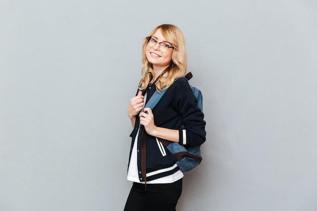 Bastante joven estudiante con gafas con mochila