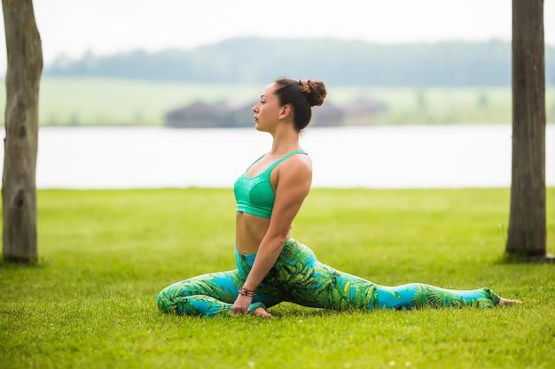 Bastante joven haciendo ejercicios de yoga en el parque