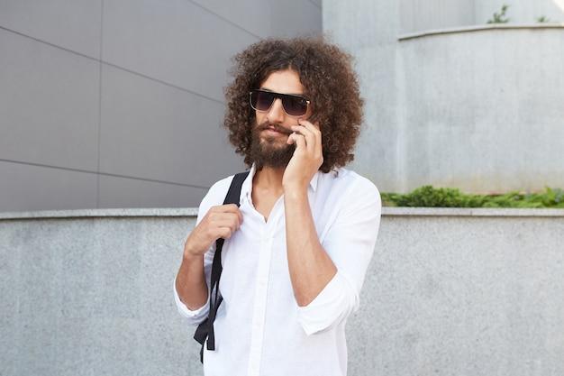 Bastante joven hombre rizado con barba caminando por la calle en un día soleado mientras habla por teléfono, vestido con camisa blanca y mochila negra