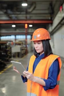 Bastante joven ingeniera seria en casco y ropa de trabajo con panel táctil mientras mira a través de datos en línea