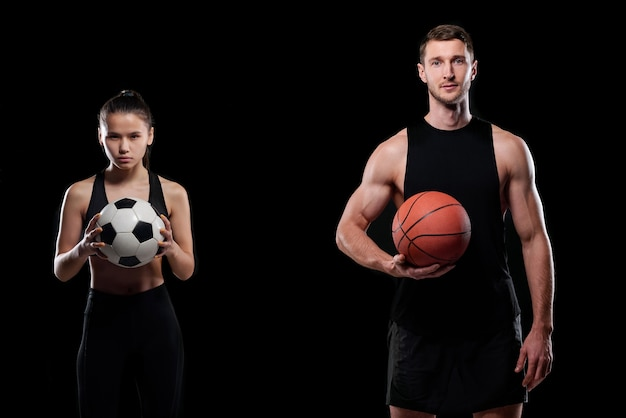 Bastante joven jugador de fútbol y baloncesto masculino musculoso sosteniendo bolas mientras está de pie