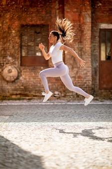 Bastante joven juping alto durante el entrenamiento en el entorno urbano