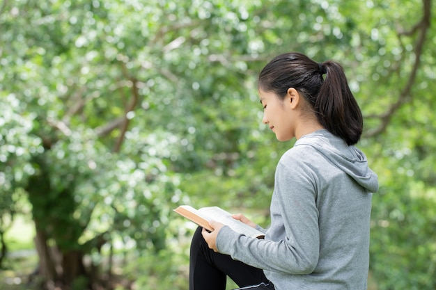 Bastante joven leyendo la biblia en el parque. leyendo un libro. el concepto de la biblia de dios se basa en la fe y la espiritualidad.
