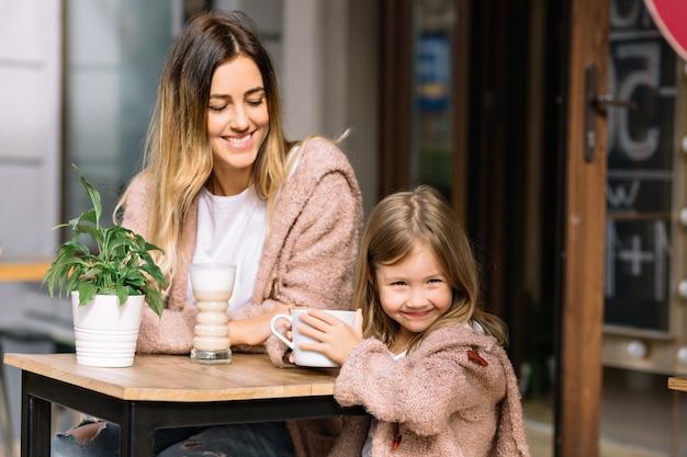 Bastante joven madre con hermosa hija vestida con suéteres calientes está sentada en la cafetería